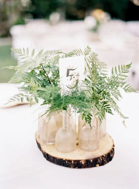 a rustic centerpiece with a wood slice, some ferns in bottles and a table number is very easy to DIY