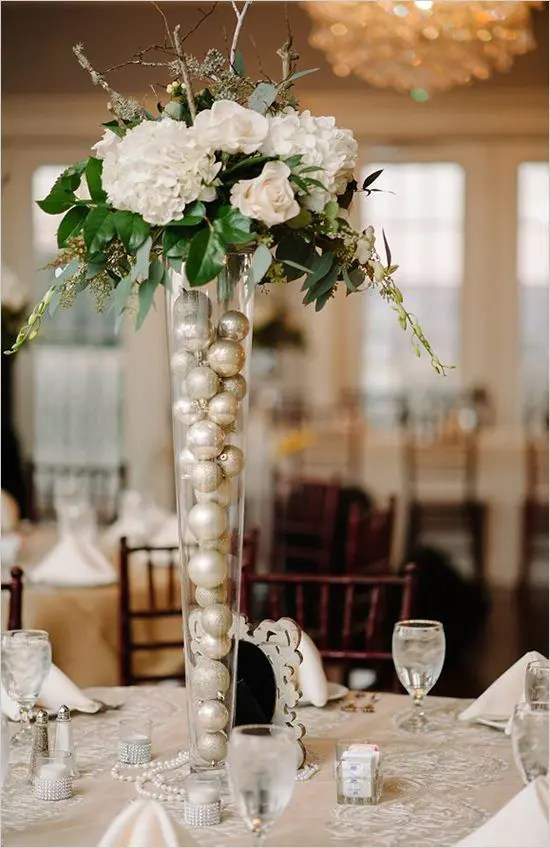 a white bloom, eucalyptus, branches wedding centerpiece in a tall vase filled with pearly Christmas ornaments for a winter wedding