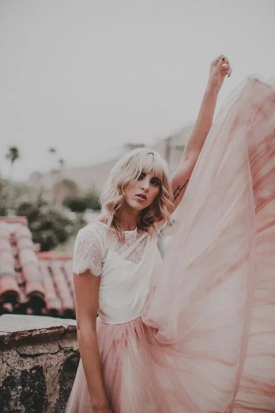 a white lace top with short sleeves and a pink pleated skirt for a romantic and girlish bridal look