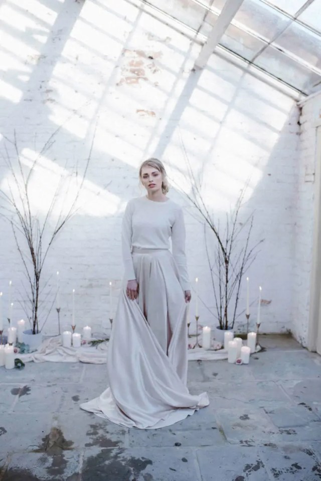 a minimalist wedding ensemble with a plain pleated skirt and a neutral top with long sleeves
