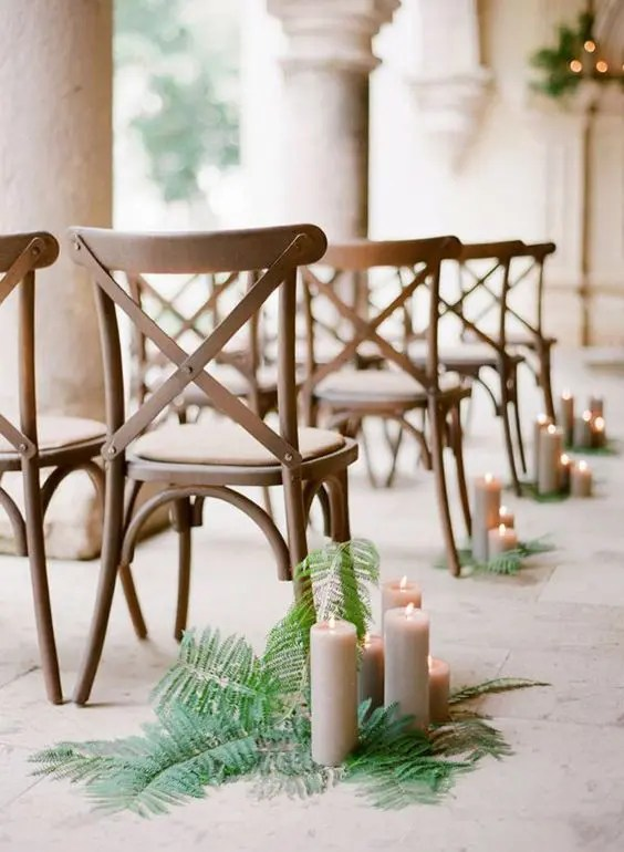 ferns placed on the floor and taupe candles placed right on them look natural and fresh