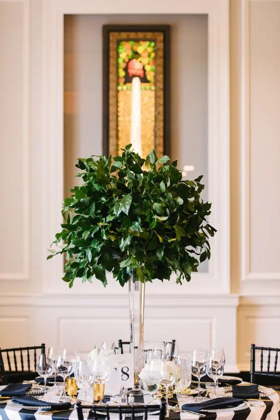 an ultra-modern tall centerpiece of a clear vase and foliage looks amazing and follows the non-floral wedding trend