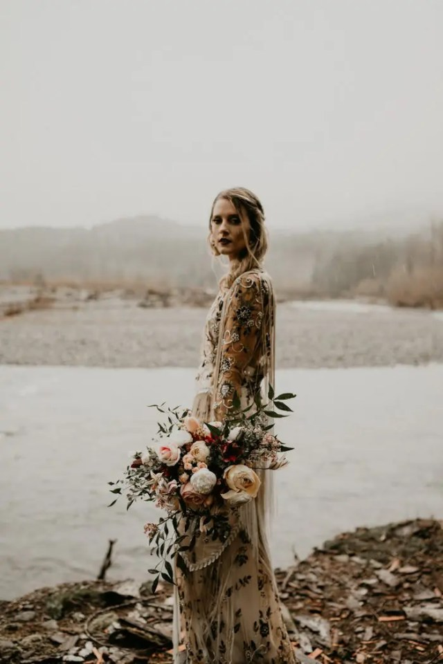 a catchy embroidered wedding dress with long fringe and a very dark maroon lipstick for a boho bridal look