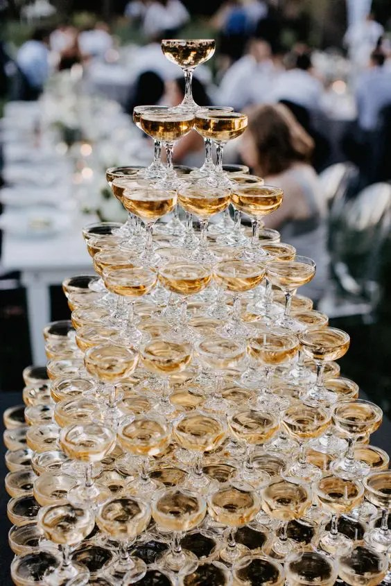 a very large champagne tower is a gorgeous idea for any wedding, your guests will love it