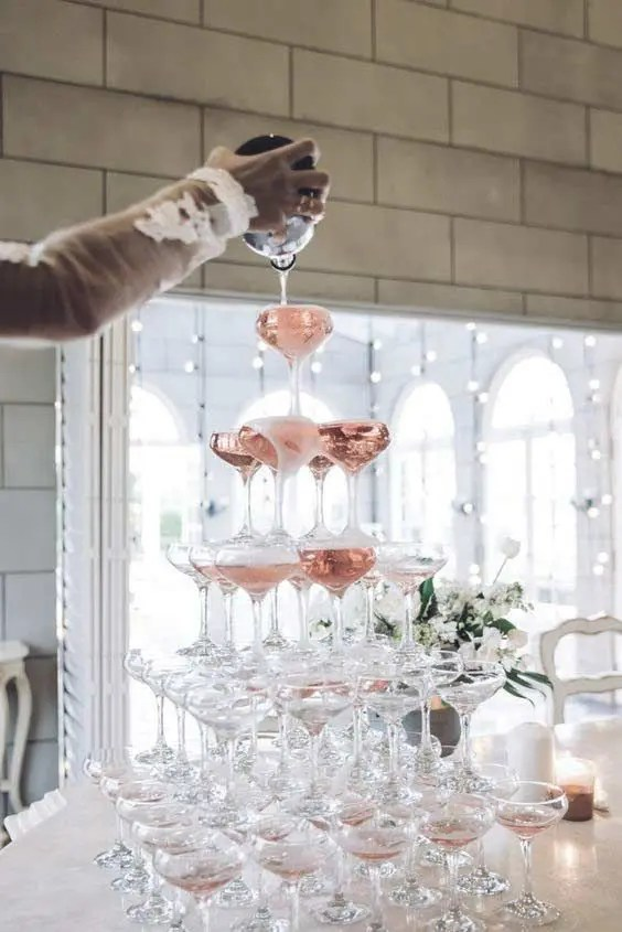 an elegant champagne tower with pink champagne is an amazing glam and sparkling idea