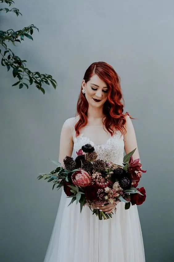 red hair and a very dark burgundy lip make the romantic bridal look balanced and more rock-like