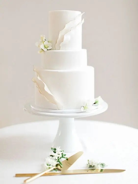a chic white wedding cake with textural touches and gold edging plus fresh white flowers, modern classics