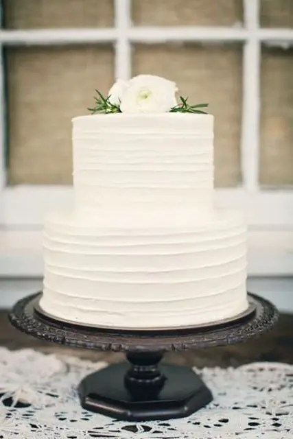 a textural white wedding cake with white blooms on top is a great idea to rock classic whites but spruce them up with a texture