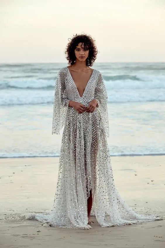 a stunning plunging neckline wedding dress with bell sleeves fully covered with silver sequins to imitate fish scales