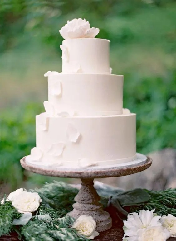 a gorgeous white wedding cake with white sugar flowers and petals falling down for a wow effect