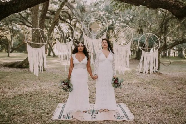 a boho chic ceremony space with white yarn dreamcatchers and a boho rug for an outdoor boho ceremony