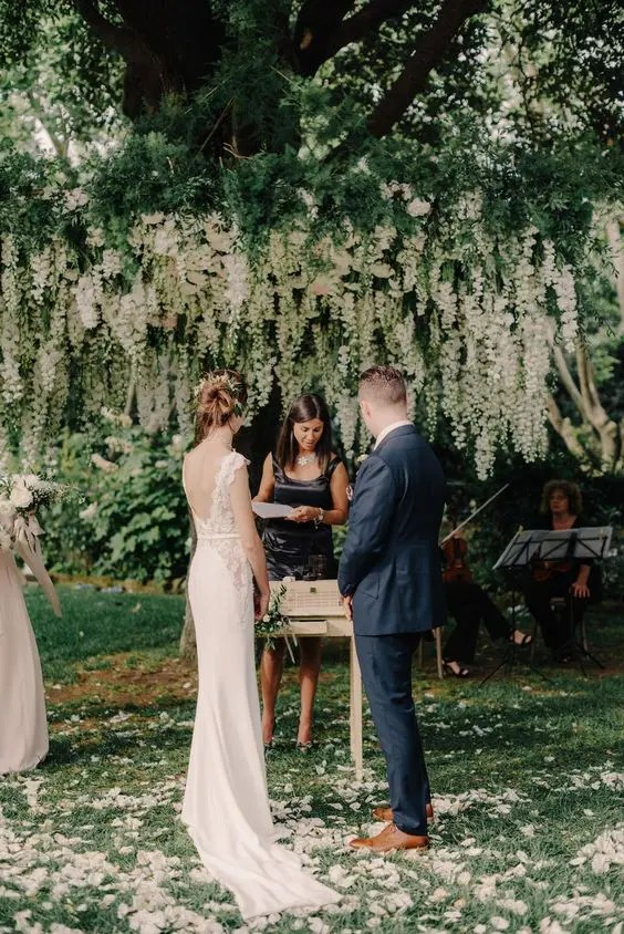 a hanging flower installation of white blooms and greenery is a very refined idea and works well for garden weddings