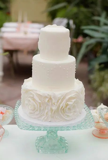 a whimsical three-tier wedding cake with sugar flowers and pearls for a vintage feel