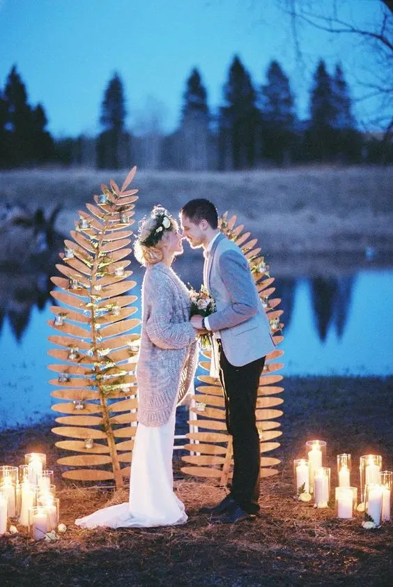 a nature-inspired wedding backdrop of two wooden fern leaves decorated with greenery and with candles around