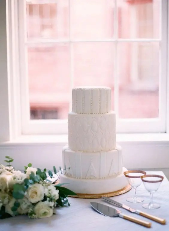 an all-white wedding cake with unique frosting textures, all different for each tier is a modern and fresh idea