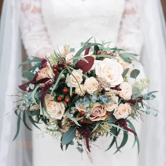 a classic Christmas wedding bouquet of blush roses, eucalyptus and holly berries