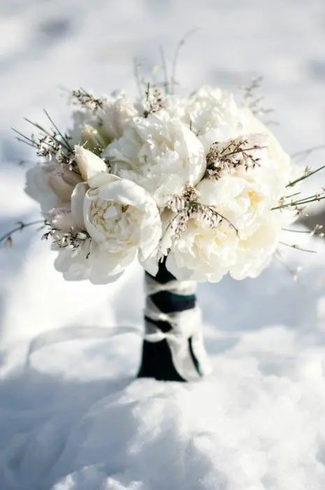 a white winter wedding bouquet with white and blush blooms and textural flowers plus a contrasting wrap