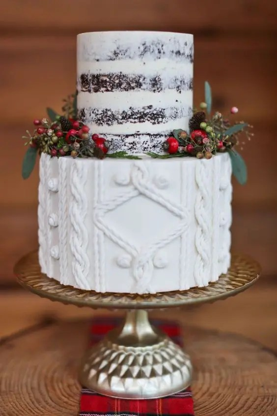 a Christmas wedding cake with a naked part and a cable knit one plus berries and little pinecones around