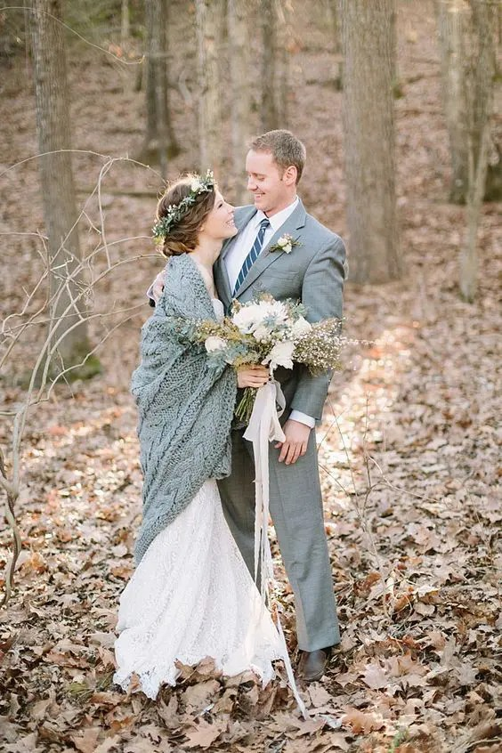 a grey suit for the groom and a grey knit coverup for the bride is a chic idea for a winter wedding and for couple's portraits