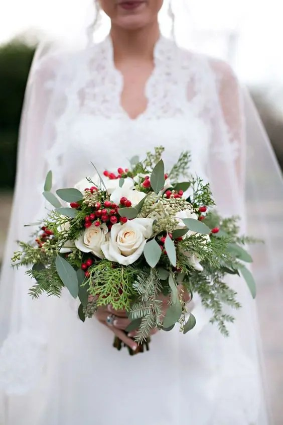 an effortlessly chic wedding bouquet with evergreens, foliage, holly berries and white roses