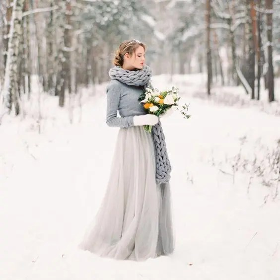 a grey wedding gown, a grey sweater over it, a grey chunky knit scarf and white mittens