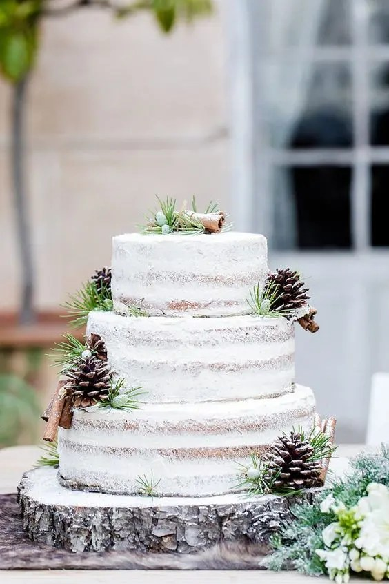 A Naked Wedding Cake With Piecones Cinnamon Bark And Greeneery To Follow The Trend Of