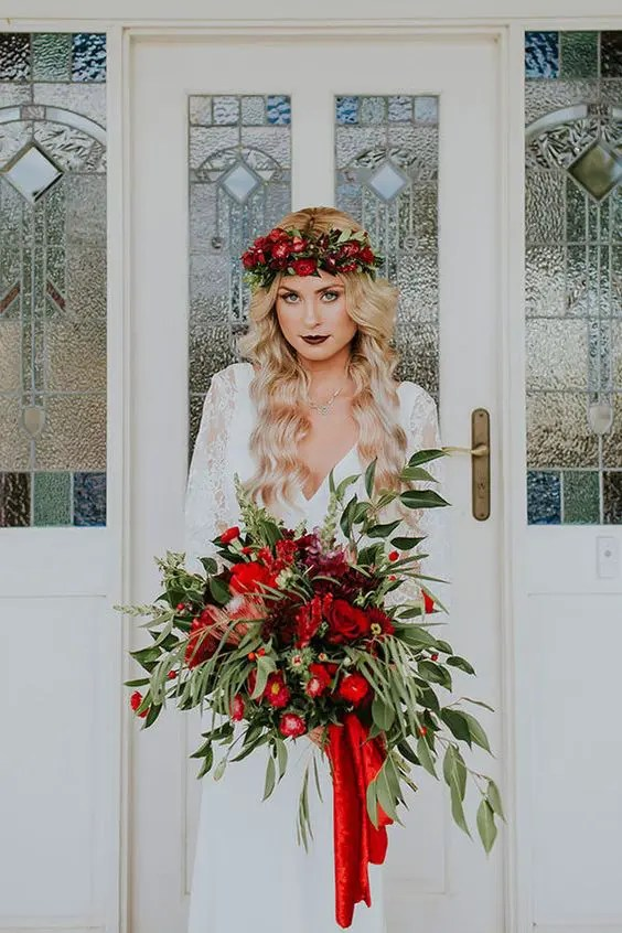 a lush cascading Christmas wedding bouquet with greenery and red blooms is Christmas classics