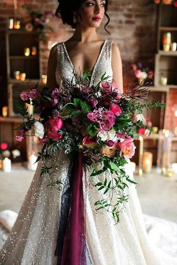 a super lush and refined wedding bouquet in the shades of pink, burgundy, orange, with berries and greenery of various kinds