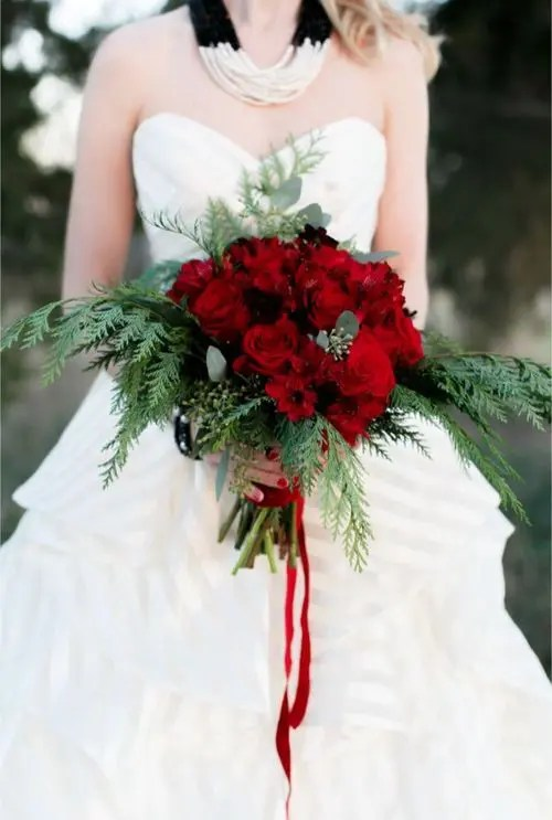 a Christmas wedding bouquet of evergreens, eucalyptus and red roses plus red ribbons
