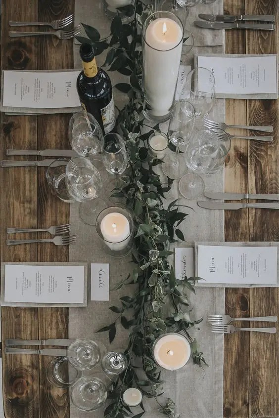 a grey table runner and napkins plus white candles and fresh greenery for a simple rustic look