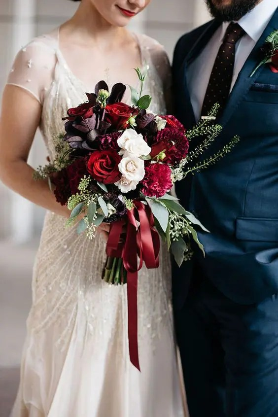 a luxurious wedding bouquet in the shads of red, deep purple and white with eucalyptus and red ribbons