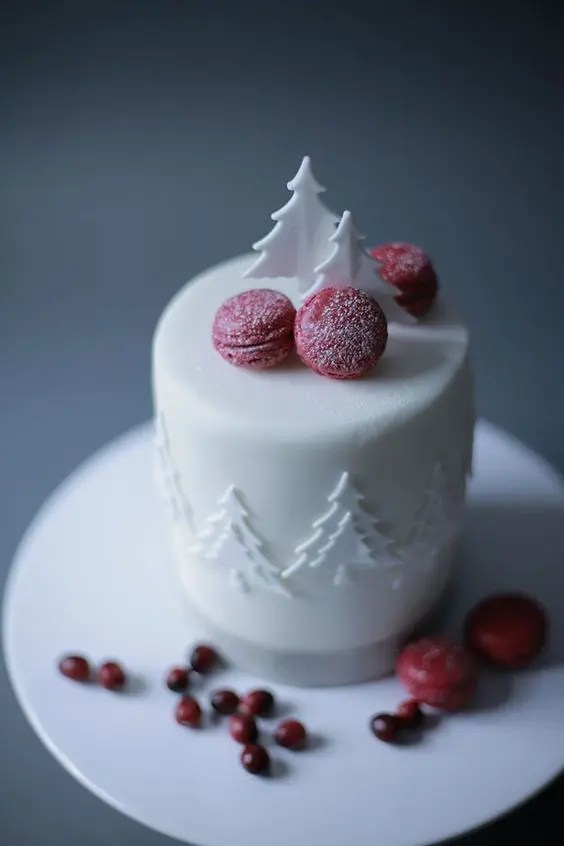 a white wedding cake with sugar trees and sugared cranberry macarons is a bright modern idea for Christmas