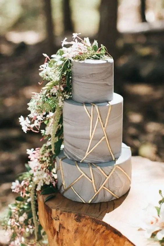 a grey marbleized cake decorated with gold geometric touches and cascading greenery and blooms