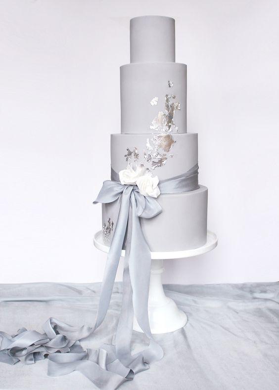 a dove grey wedding cake with a grey ribbon bow and silver leaf for a minimalist winter wedding