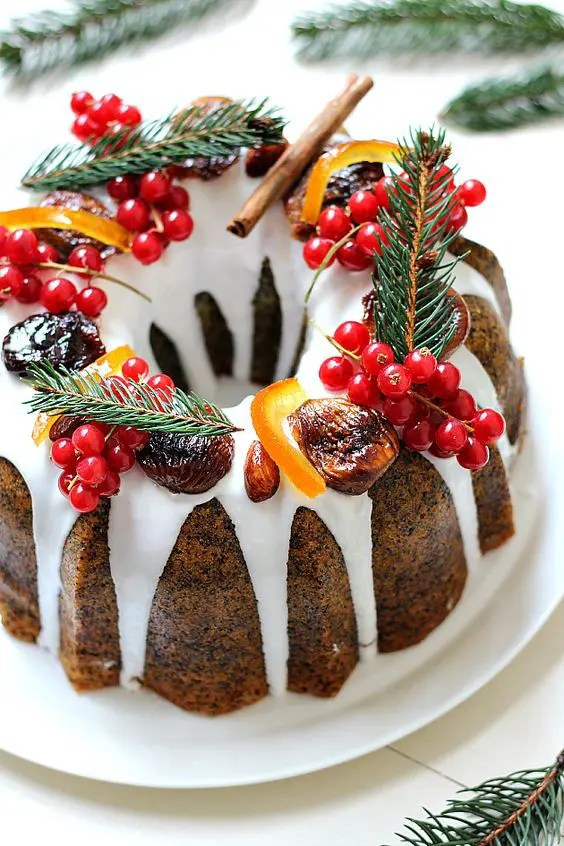 a poppy seed bundt wedding cake with white chocolate drip, cranberries, evergrenes, cinnamon and candied fruit