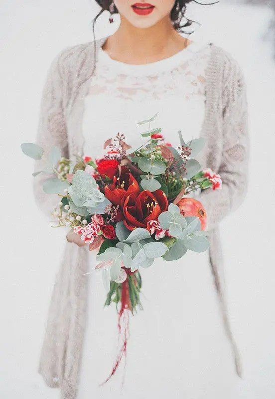 a tender bouquet with red blooms, pomegranate, eucalyptus and dark foliage for a Christmas wedding