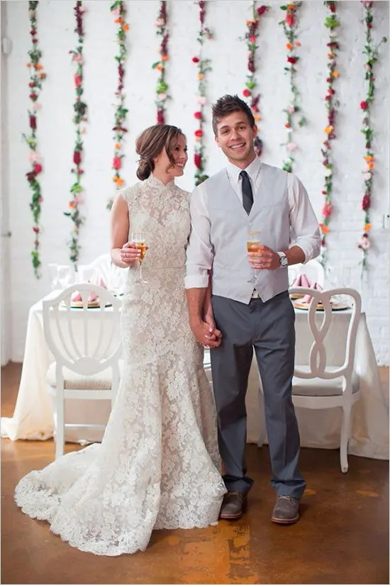 a romantic lace mermaid wedding dress with a high neckline and a train, the groom wearign grey pants, a waistcoat and a tie