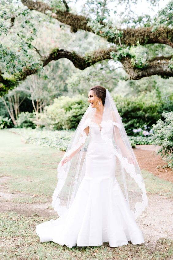 an off the shoulder plain mermaid wedding gown with a deep neckline and a train for a formal wedding