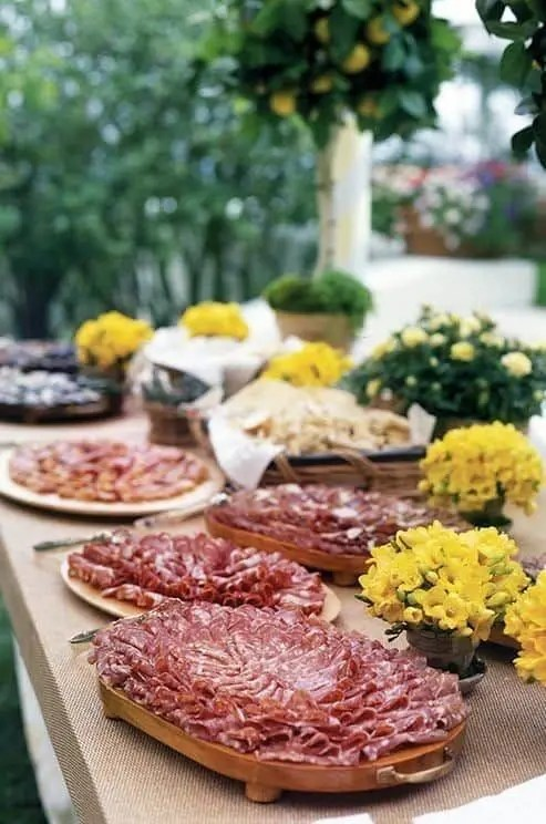 a charcuterie table with lots of salami and prosciutto served on wooden trays