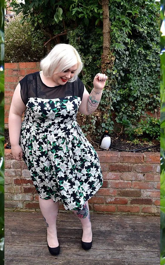 a floral midi dress with a sheer black top, black shoes for a stylish spring or summer wedding guest look