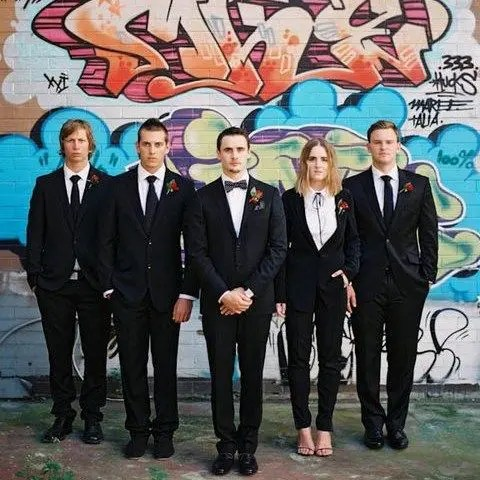 everyone wearing black suits, a bolo tie for the girl. ties and bow ties for the guys and sexy heels for the lady