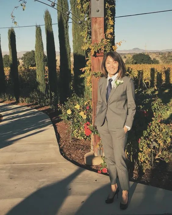 a grey suit with cropped pants, a navy tie, black heels and a floral boutonniere for an elegant look