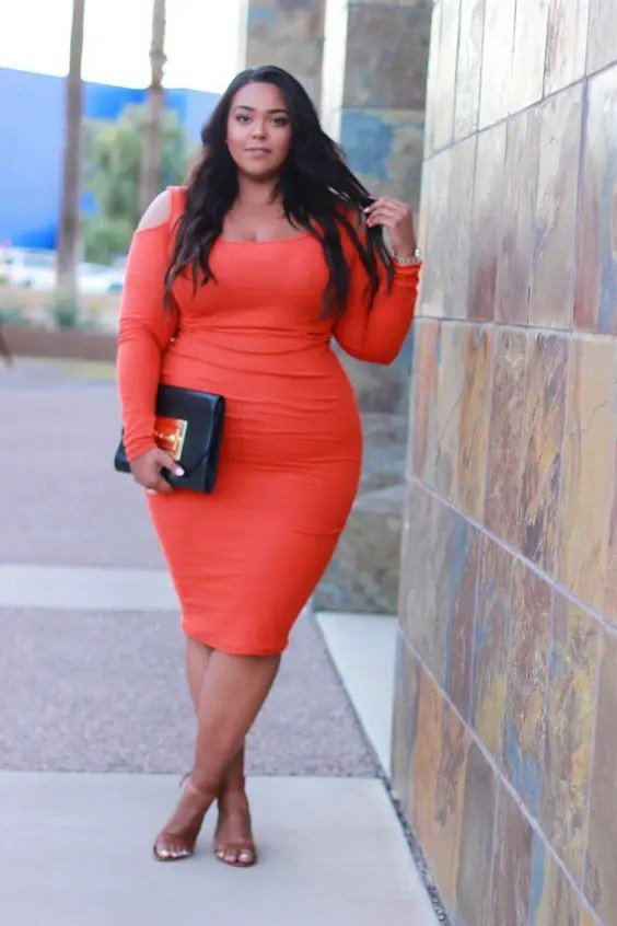 an orange cold shoulder midi dress with long sleeves, tan shoes and a black and gold clutch