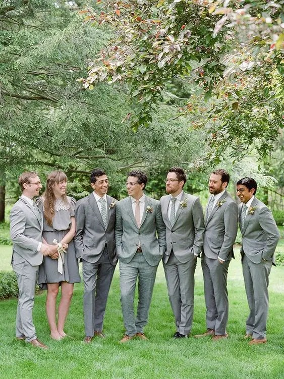 groomsmen wearing grey suits and a groomswoman rocking a grey over the knee dress with a lace top