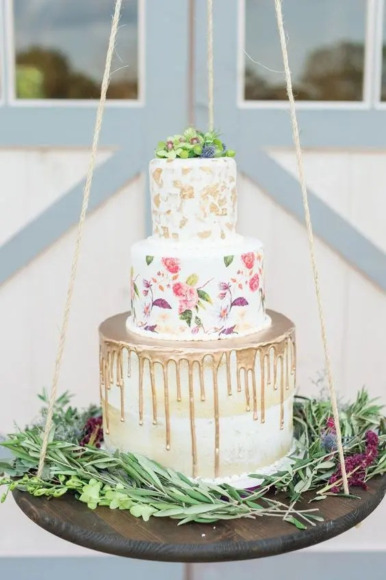 a trendy wedding cake combining metallic drip, handpainting and metallic leaf plus fresh blooms on top
