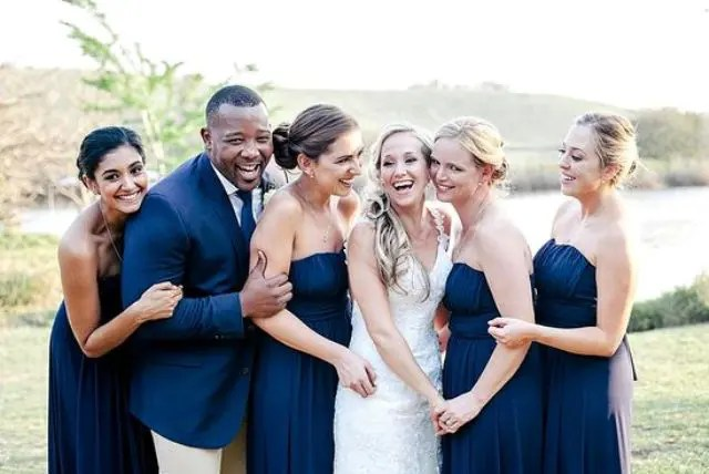 everyone wearing navy, strapless gowns for the girls and a navy blazer plus a tie for the groomsman