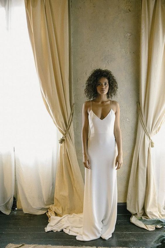 a minimalist spaghetti strap wedding dress with a sweep train