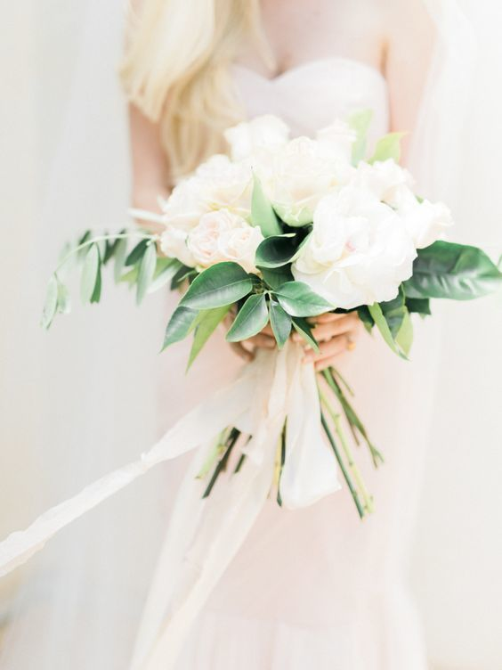 a simple and modern wedding bouquet of blush blooms and some greenery plus matching ribbons