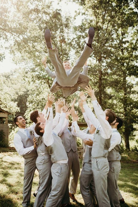 a groom praised by his groomsmen is a fun photo idea that will easily substitute a usual portrait with your friends