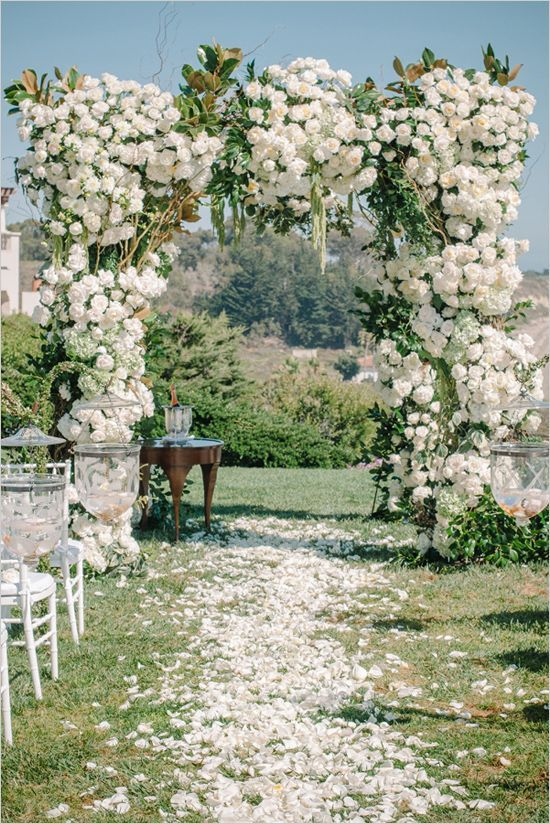 a gorgeous and super lush wedding arch with neutral roses and magnolia leaves for a summer wedding